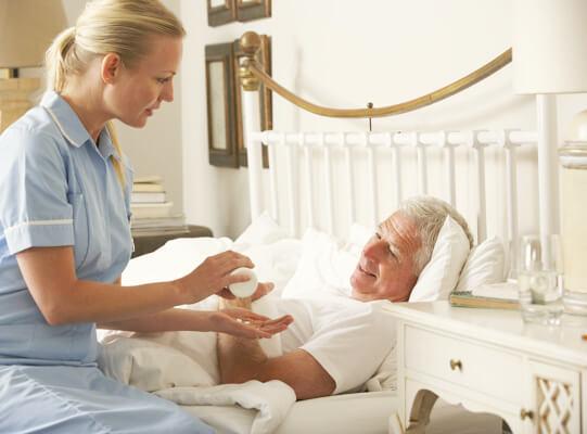 nurse giving medicine to elder man