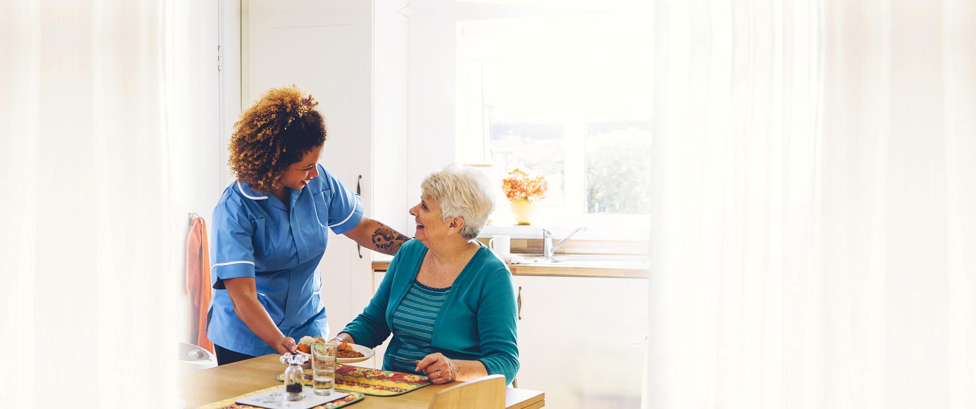 caregiver serving food for elder woman