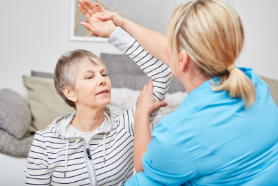 caregiver makes occupational therapy exercise with senior woman